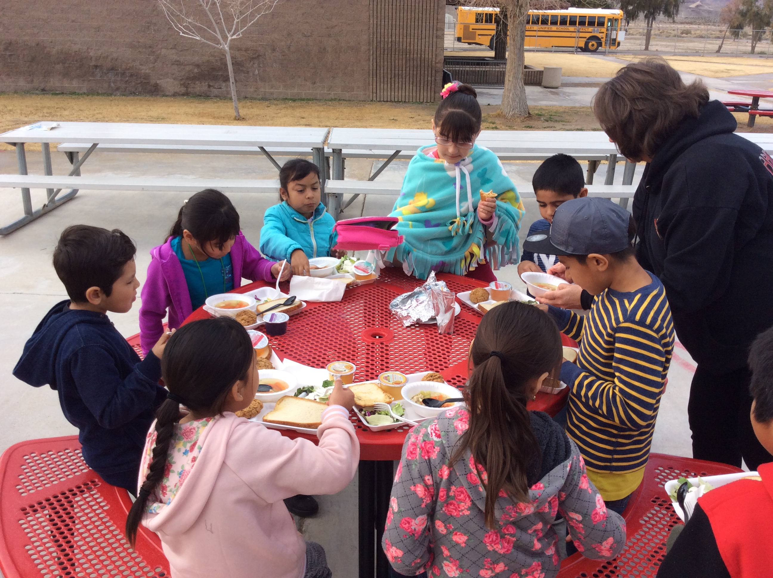 Superintendent and students having stone soup lunch.
